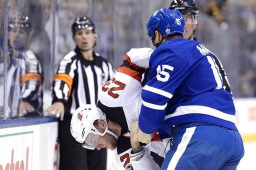 Toronto Maple Leafs left wing Matt Martin (15) and New Jersey Devils right wing Stefan Noesen (23) fight during the first period of an NHL hockey game Wednesday, Oct. 11, 2017, in Toronto. (Nathan Denette/The Canadian Press via AP)