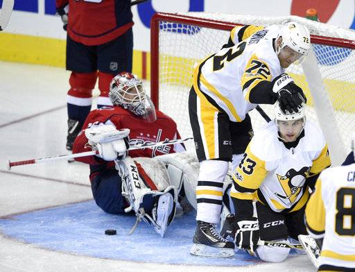 Pittsburgh Penguins left wing Conor Sheary (43) celebrates his goal with right wing Patric Hornqvist (72), of Sweden, during the third period of an NHL hockey game as Washington Capitals goalie Braden Holtby, sits on the ice, Wednesday, Oct. 11, 2017, in Washington. The Penguins won 3-2.