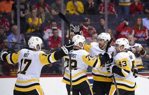 Pittsburgh Penguins defenseman Kris Letang (58) celebrates his goal with Conor Sheary (43), Patric Hornqvist (72) and Bryan Rust (17) during the first period of an NHL hockey game against the Washington Capitals, Wednesday, Oct. 11, 2017, in Washington.