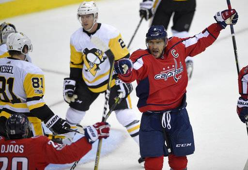 Washington Capitals left wing Alex Ovechkin (8), of Russia, celebrates his goal with Christian Djoos, lower left, of Sweden, during the third period of an NHL hockey game against the Pittsburgh Penguins, Wednesday, Oct. 11, 2017, in Washington. Also seen are Penguins right wing Phil Kessel (81) and defenseman Chad Ruhwedel (2). The Penguins won 3-2.