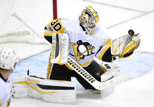 Pittsburgh Penguins goalie Matt Murray (30) reaches for the puck during the third period of an NHL hockey game against the Washington Capitals, Wednesday, Oct. 11, 2017, in Washington. The Penguins won 3-2.