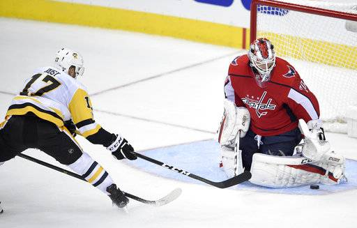 Washington Capitals goalie Braden Holtby (70) stops the puck against Pittsburgh Penguins right wing Bryan Rust (17) during the third period of an NHL hockey game, Wednesday, Oct. 11, 2017, in Washington. The Penguins won 3-2.