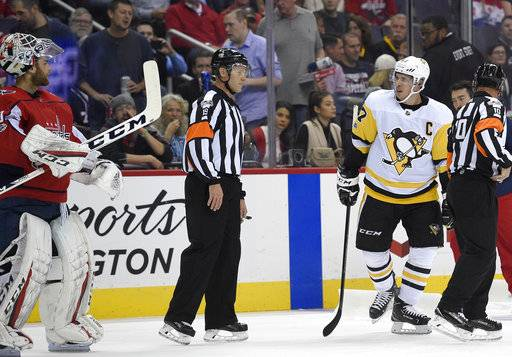 Pittsburgh Penguins center Sidney Crosby (87) and Washington Capitals goalie Braden Holtby, left, look at each other during a break in the action in the first period of an NHL hockey game, Wednesday, Oct. 11, 2017, in Washington.