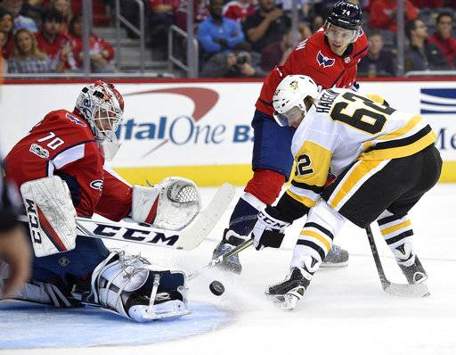 Pittsburgh Penguins left wing Carl Hagelin (62), of Sweden, battles for the puck against Washington Capitals goalie Braden Holtby (70) during the first period of an NHL hockey game, Wednesday, Oct. 11, 2017, in Washington. Also seen is Capitals defenseman John Carlson (74).