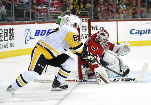Washington Capitals goalie Braden Holtby (70) stops the puck against Pittsburgh Penguins center Sidney Crosby (87) during the first period of an NHL hockey game, Wednesday, Oct. 11, 2017, in Washington.