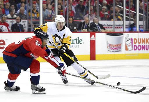 Pittsburgh Penguins center Evgeni Malkin (71), of Russia, chases the puck against Washington Capitals right wing Devante Smith-Pelly (25) during the first period of an NHL hockey game, Wednesday, Oct. 11, 2017, in Washington.