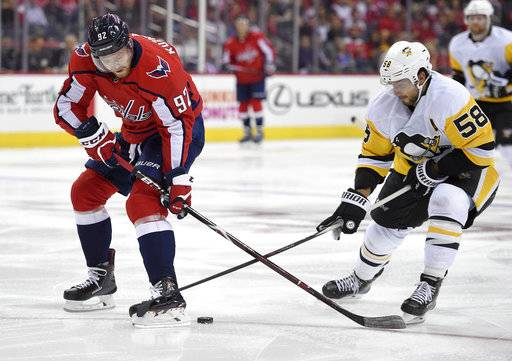 Washington Capitals center Evgeny Kuznetsov (92), of Russia, battles for the puck against Pittsburgh Penguins defenseman Kris Letang (58) during the second period of an NHL hockey game, Wednesday, Oct. 11, 2017, in Washington.