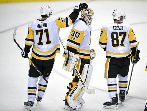 Pittsburgh Penguins goalie Matt Murray (30) celebrates with Evgeni Malkin (71), of Russia, and Sidney Crosby after an NHL hockey game against the Washington Capitals, Wednesday, Oct. 11, 2017, in Washington. The Penguins won 3-2.