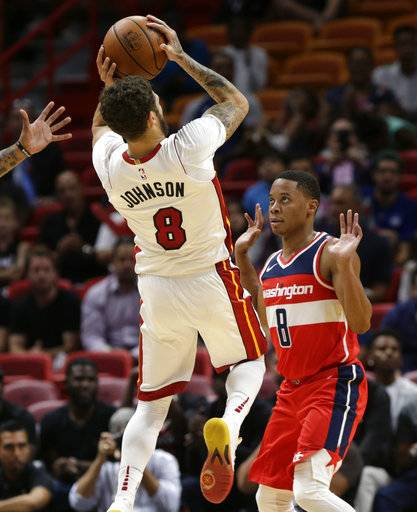 Miami Heat's Tyler Johnson (8) shoots over Washington Wizards' Tim Frazier (8) during the first half of a preseason NBA basketball game, Wednesday, Oct. 11, 2017, in Miami.