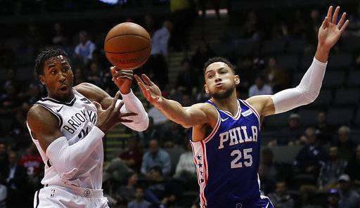 Brooklyn Nets forward Rondae Hollis-Jefferson, left, and Philadelphia 76ers guard Ben Simmons (25) reach for a rebound during the first quarter of a preseason NBA basketball game, Wednesday, Oct. 11, 2017, in Uniondale, N.Y.