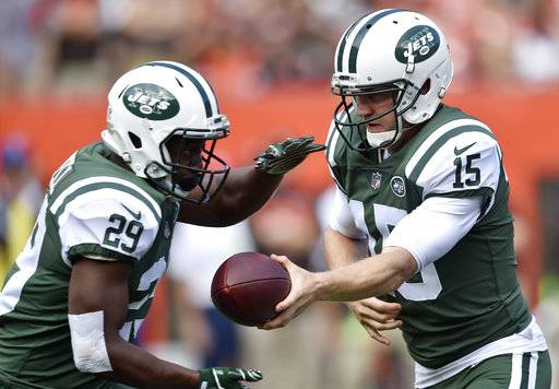 New York Jets quarterback Josh McCown, right, hands off the ball to running back Bilal Powell during the first half of an NFL football game against the Cleveland Browns, Sunday, Oct. 8, 2017, in Cleveland. (AP Photo/David Richard)