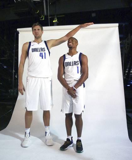 FILE - In this Sept. 25, 2017, file photo, Dallas Mavericks forward Dirk Nowitzki (41) jokingly poses for a photo with new teammate guard Dennis Smith Jr. (1) during an NBA basketball team media day, in Dallas. Nowitzki's 20th season with the Mavericks will be his first with rookie point guard Dennis Smith Jr., whose rave reviews started in summer league. (AP Photo/LM Otero, File)