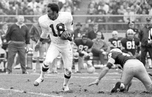 FILE - In this Oct. 25, 1970, file photo, Philadelphia Eagles Ben Hawkins (18) leaves his helmet behind as he breaks free from the Green Bay Packers Ken Ellis (48) enroute to a touchdown during an NFL football game in Milwaukee, Wis. Former Eagles wide receiver Ben Hawkins died on Monday, Oct. 9, 2017, the team said. He was 73. A third-round pick of the Eagles in 1966, Hawkins spent eight of his nine NFL seasons in Philadelphia. (AP Photo/File)