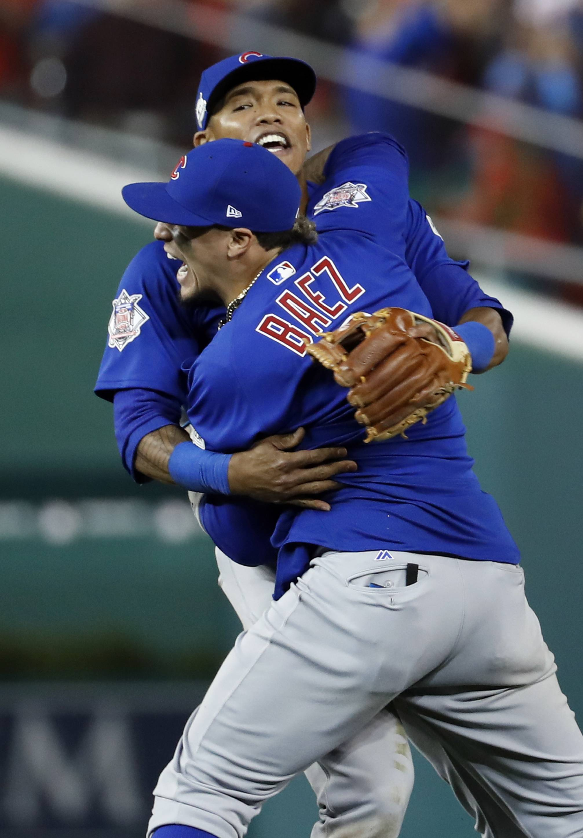 Chicago Cubs' Javier Baez (9) celebrates with teammate Addison Russell after beating the Washington Nationals 9-8 to to win baseball's National League Division Series, at Nationals Park, early Friday, Oct. 13, 2017, in Washington.