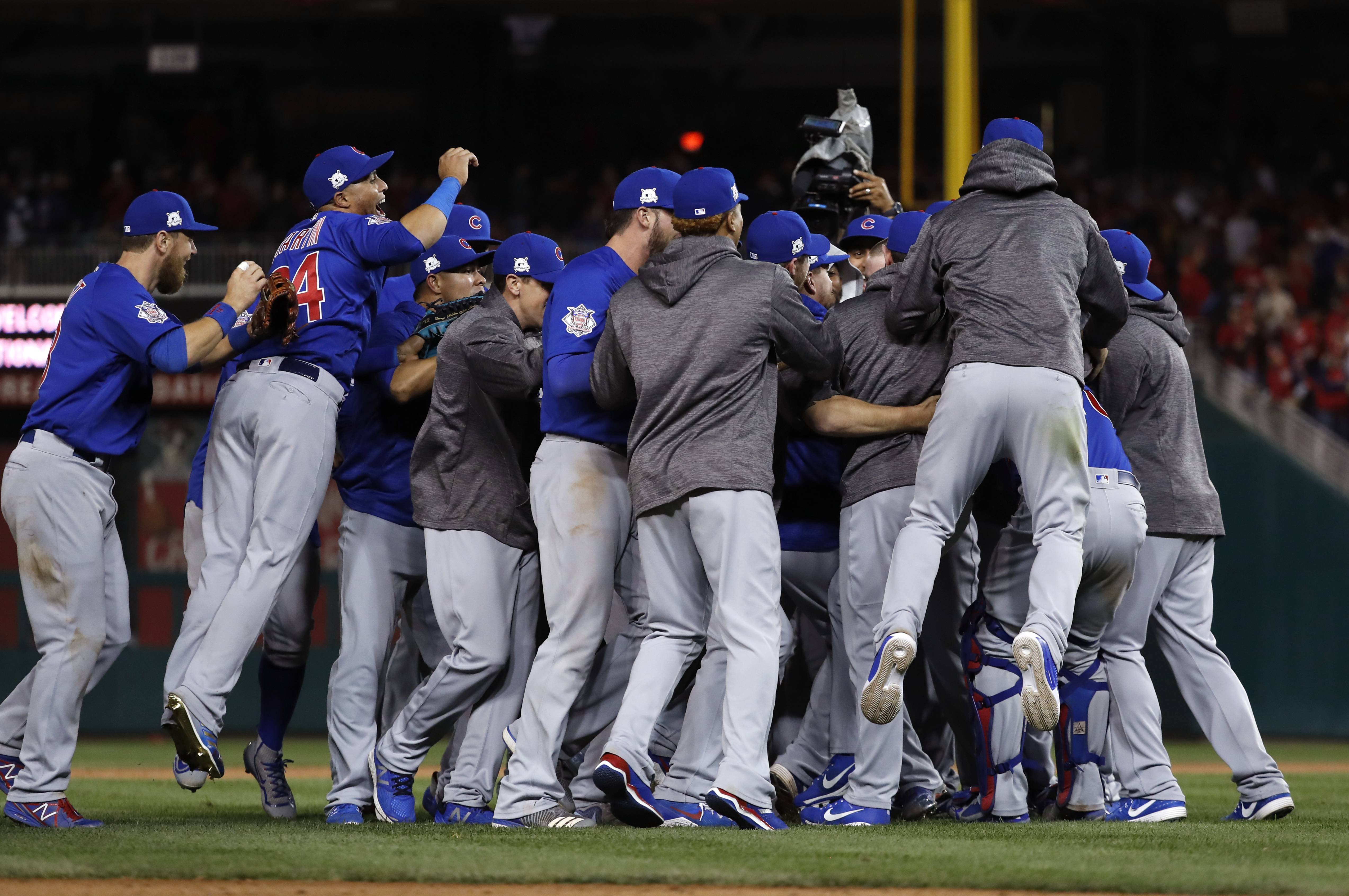 The Chicago Cubs celebrate after beating the Washington Nationals 9-8 to to win baseball's National League division series, at Nationals Park in Washington.