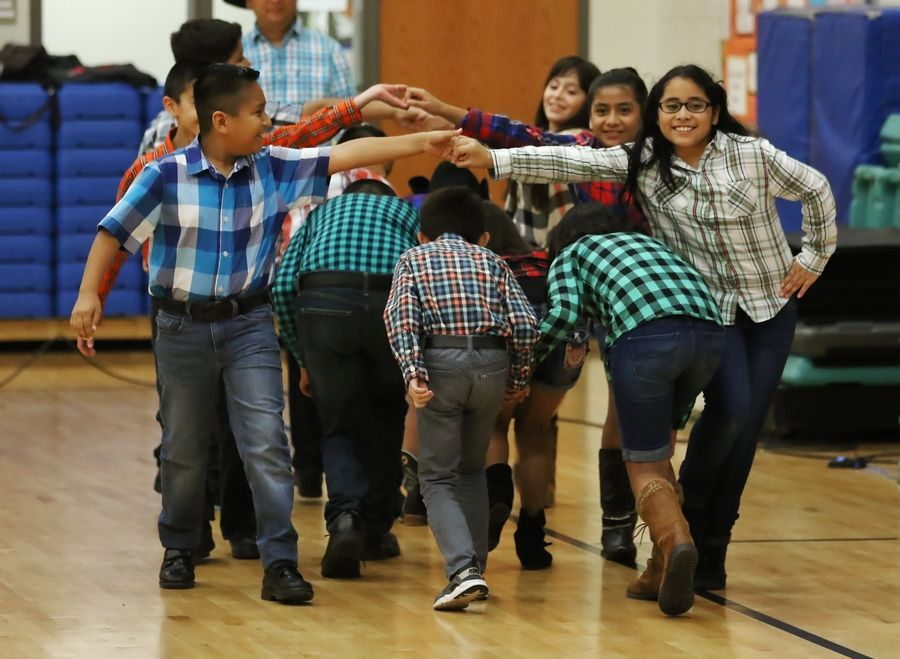 "Alberto Lozano dances with Ashley Aban as the fifth-grade class performs the ""Santa Rita"" dance during the Hispanic Heritage Celebration on Thursday at Prairie Trail School in Wadsworth. More than 300 people were entertained at the Gurnee School District 56 event."