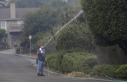 FILE - In this Oct 10, 2017, file photo, Leonard George sprays down trees in front of his house in the Oakmont area of Santa Rosa, Calif. For many residents in the path of one of California's deadliest blazes, talk is of wind direction, evacuations and goodbyes.