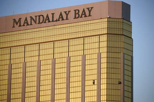 FILE - In this Monday, Oct. 2, 2017 file photo, drapes billow out of broken windows at the Mandalay Bay resort and casino on the Las Vegas Strip, following a deadly shooting at a music festival in Las Vegas. Two hotel employees had called for help and reported that gunman Stephen Paddock sprayed a hallway with bullets, striking an unarmed security guard in the leg, several minutes before Paddock opened fire from the resort on a crowd below at a musical performance, killing dozens of people and injuring hundreds.