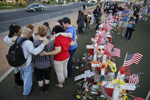 FILE - In this Monday, Oct. 9, 2017 file photo, people pray at a makeshift memorial for victims of a mass shooting in Las Vegas. Gunman Stephen Paddock opened fire Sunday, Oct. 1 from a room at the Mandalay Bay resort and casino, on an outdoor country music concert killing dozens and injuring hundreds. A revised chronology given by investigators for the Las Vegas massacre is intensifying pressure for police to explain how quickly they responded to what would become the deadliest mass shooting in modern U.S. history.