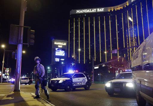 FILE - In this Sunday, Oct. 1, 2017 file photo, police officers stand along the Las Vegas Strip near the Mandalay Bay resort and casino during a shooting at a country music festival, in Las Vegas. Police initially said Stephen Paddock stopped firing on the music festival concert crowd below to shoot through his door and wound a Mandalay Bay security guard who was outside. On Monday, Oct. 9, 2017, they said the guard actually was wounded before Paddock started the massacre.