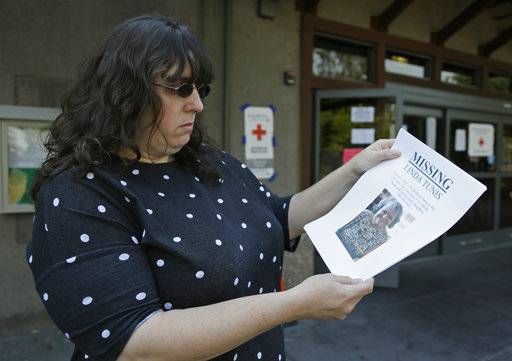 Jessica Tunis stands outside a Red Cross evacuation center and holds a flyer about her missing mother Wednesday, Oct. 11, 2017, in Santa Rosa, Calif. Tunis is searching for her missing mother, Linda Tunis, who was living at a mobile home park when wildfires struck.