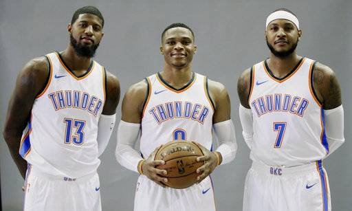 FILE - In this Sept. 25, 2017, file photo, Oklahoma City Thunder's Paul George (13), Russell Westbrook, center, and Carmelo Anthony (7) pose for a photo during an NBA basketball media day in Oklahoma City. Westbrook is a two-time scoring champion, two-time All-Star MVP and the reigning league MVP. Anthony is a 10-time All-Star and three-time Olympic gold medalist. George is a four-time All-Star, former Most Improved Player and an Olympic gold medalist. None of the new Oklahoma City Thunder teammates have an NBA title.