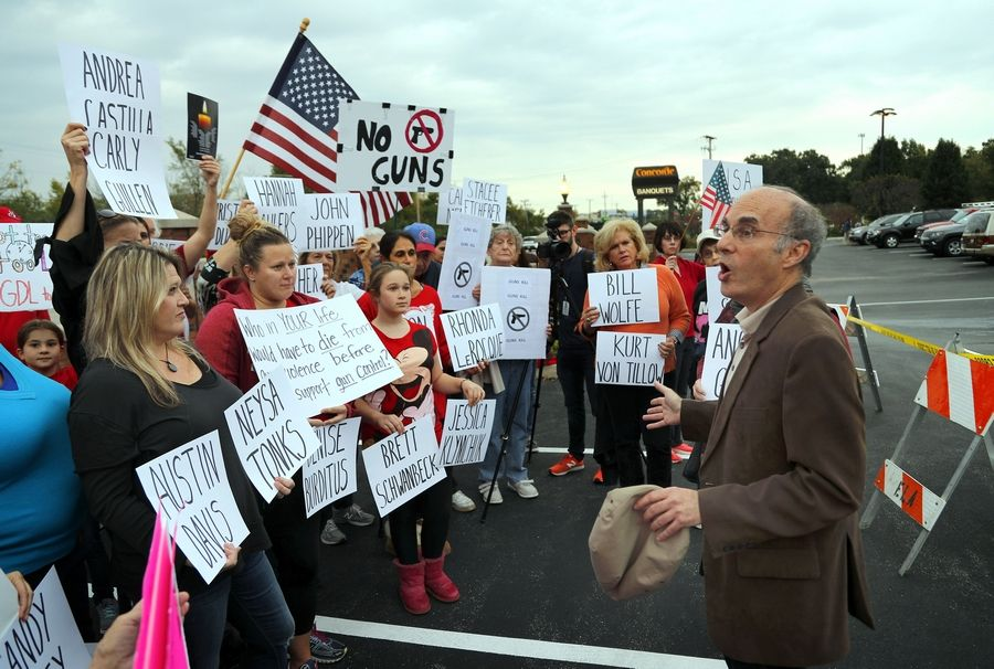 Lee Goodman of Northbrook talks to fellow protesters Friday outside Concorde Banquets in Kildeer, where the Lake County GOP was having a gun raffle as part of a fundraiser.
