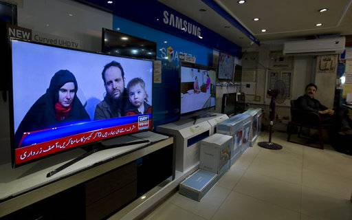 A Pakistani channel broadcasts a report about western couple, seen at a local electronic shop in Islamabad, Pakistan, Thursday, Oct. 12, 2017. An American woman, her Canadian husband and their three young children have been released after years of being held captive by a network with ties to the Taliban, U.S. and Pakistani officials said Thursday.