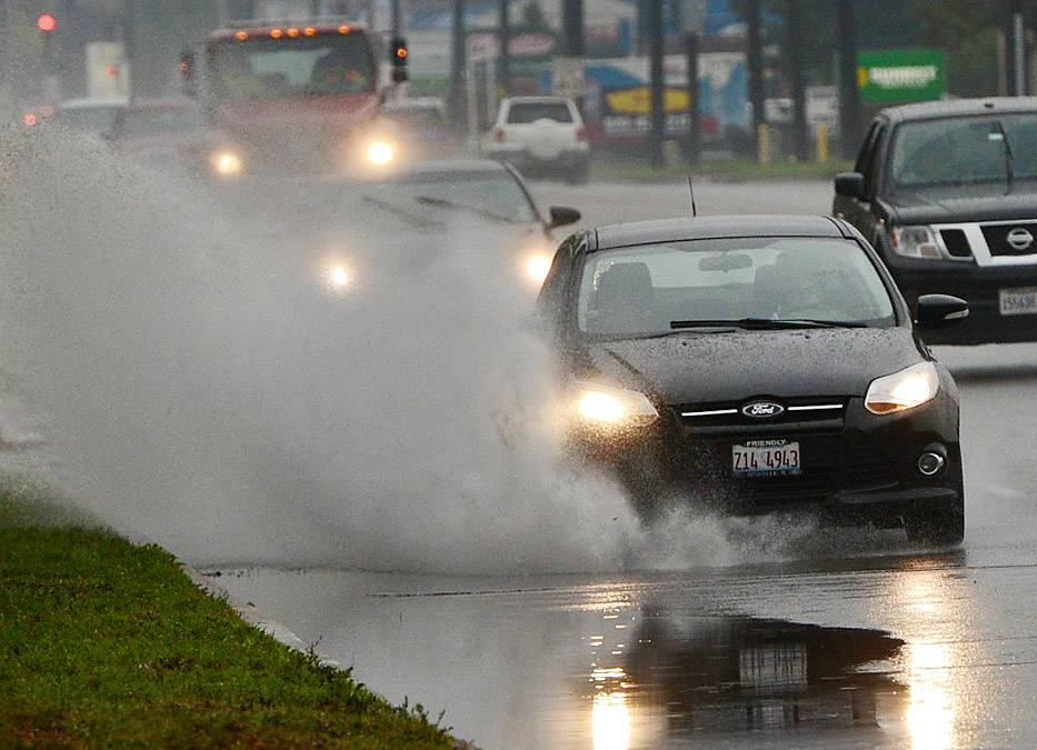 Cars splash through rain puddles along Busse Road in Mount Prospect Saturday. Drenching rainfall resulted in the National Weather Service issuing a flash flood watch for portions of Cook, DuPage, Kane, Lake, McHenry and Will counties Saturday afternoon.