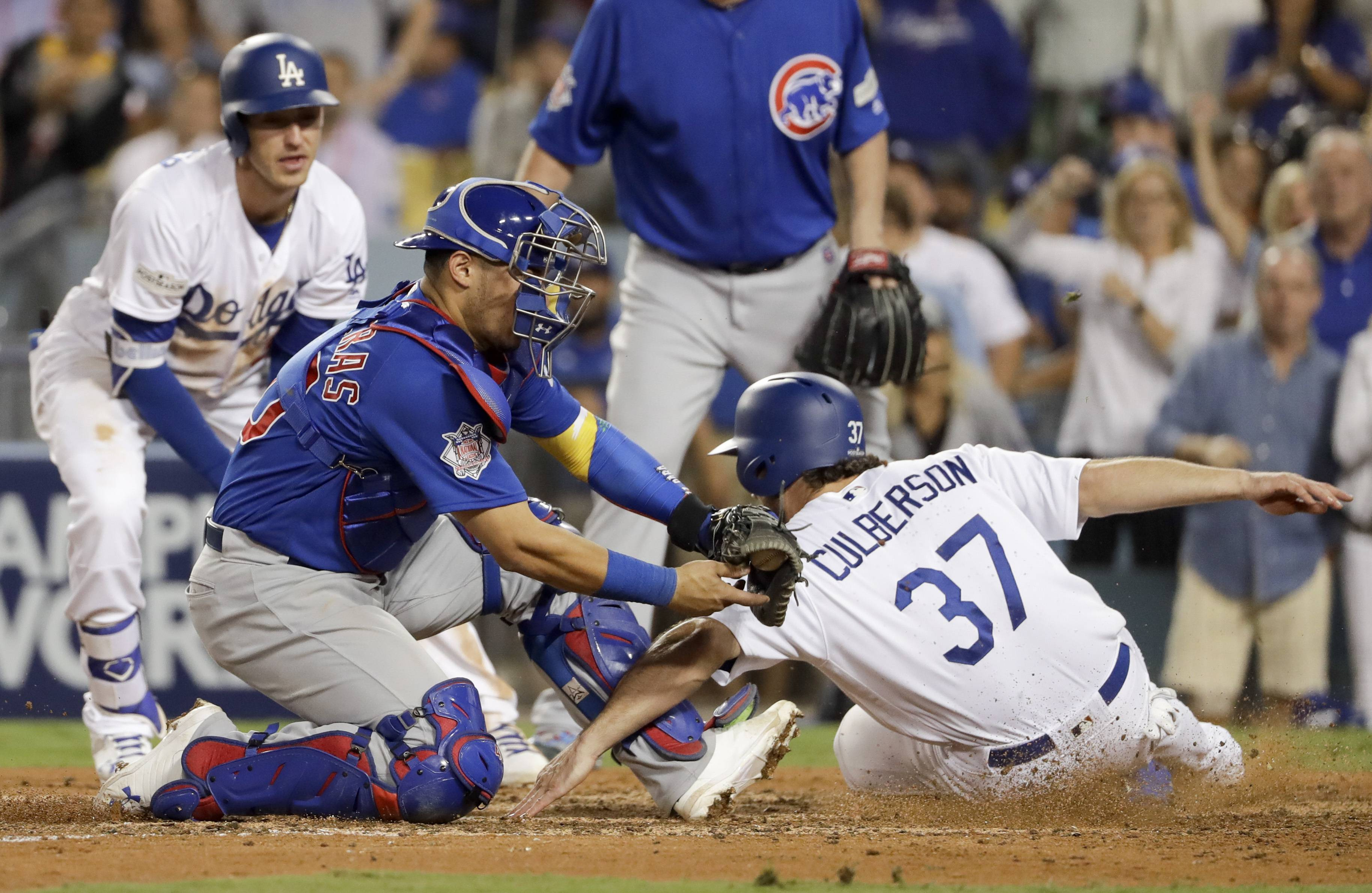 Los Angeles Dodgers' Charlie Culberson (37) is called safe at home past Chicago Cubs catcher Willson Contreras during the seventh inning of Game 1 of baseball's National League Championship Series in Los Angeles, Saturday, Oct. 14, 2017.