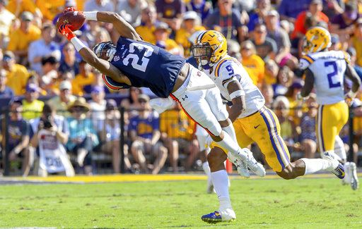 Auburn wide receiver Ryan Davis (23) stretches for a catch against LSU safety Grant Delpit (9) in the first half of an NCAA college football game in Baton Rouge, La., Saturday, Oct. 14, 2017.