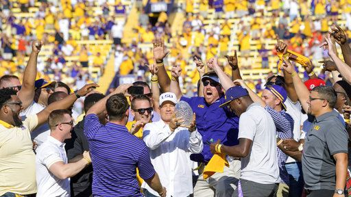 Former LSU head coach Les Miles, center, is mobbed by LSU football alumni of the 2007-8 BCS National Championship team during a halftime ceremony in an NCAA college football game against Auburn in Baton Rouge, La., Saturday, Oct. 14, 2017.