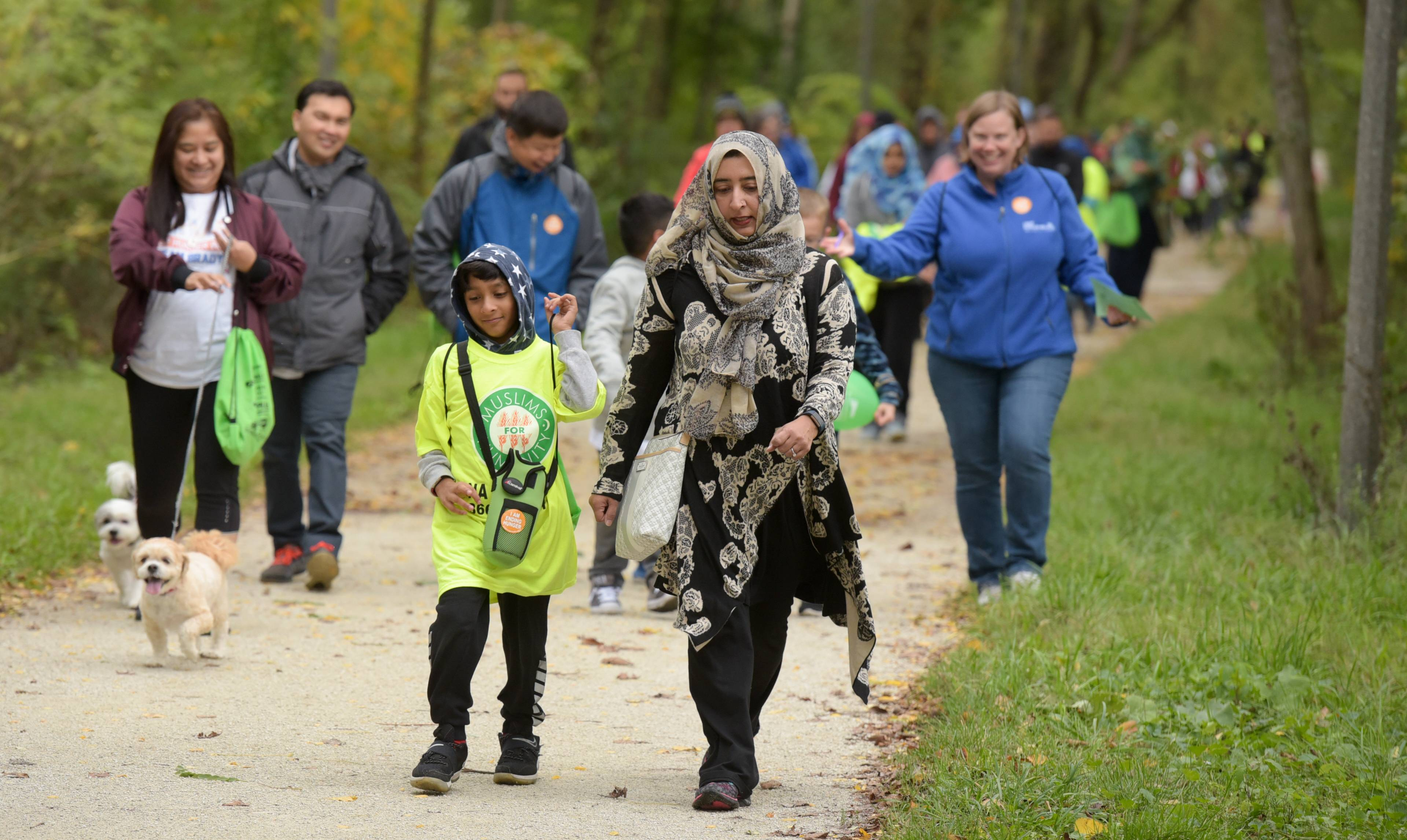 Fahteh Shahzad, 9, and his mother Munazza, of Lombard, walk along the Prairie Path on Sunday during the Great Prairie Trail CROP Walk in Lombard.