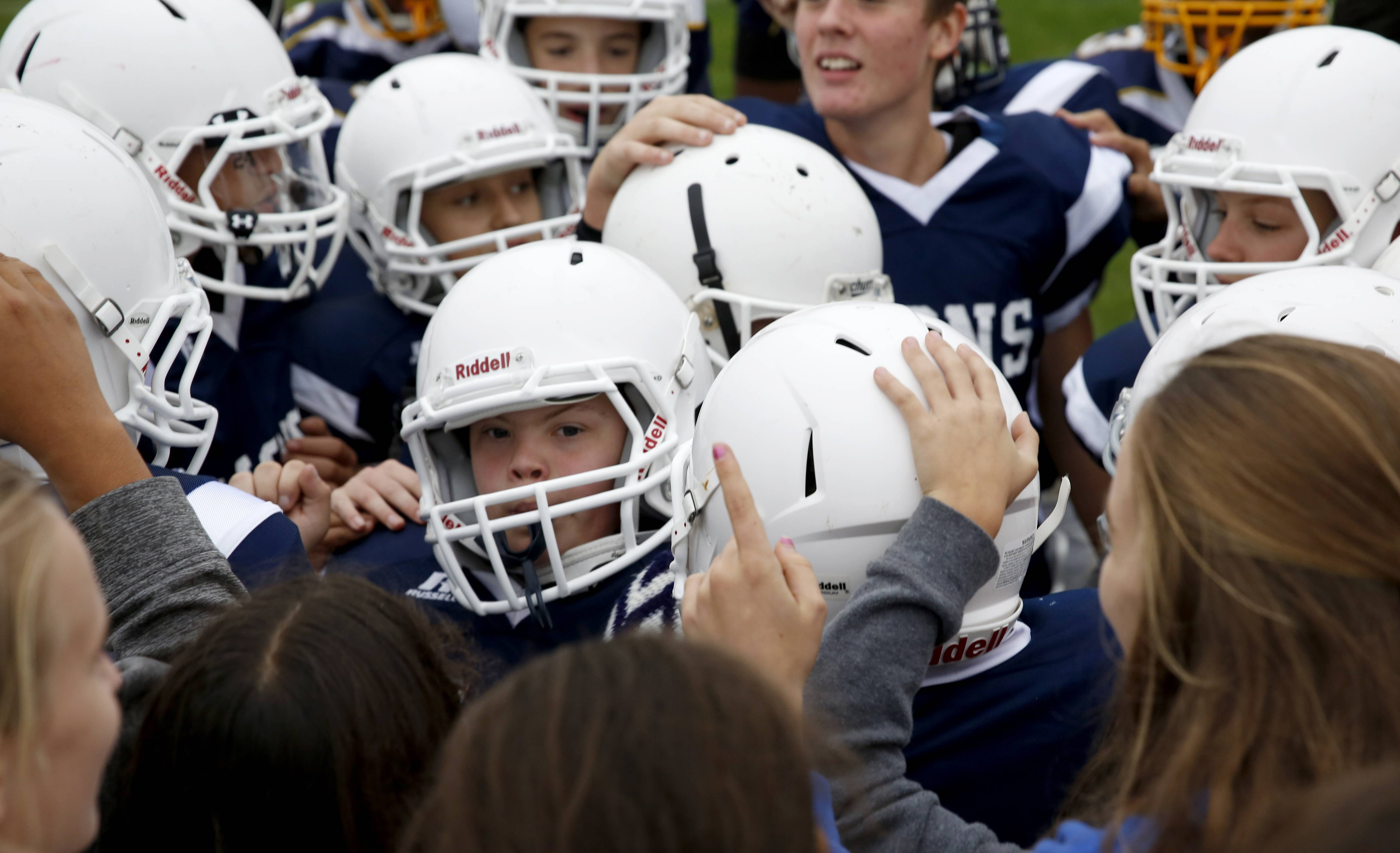 Jake Skonieczny, a Lisle Junior High School student with Down syndrome, is congratulated by teammates and fans after scoring a second quarter touchdown.
