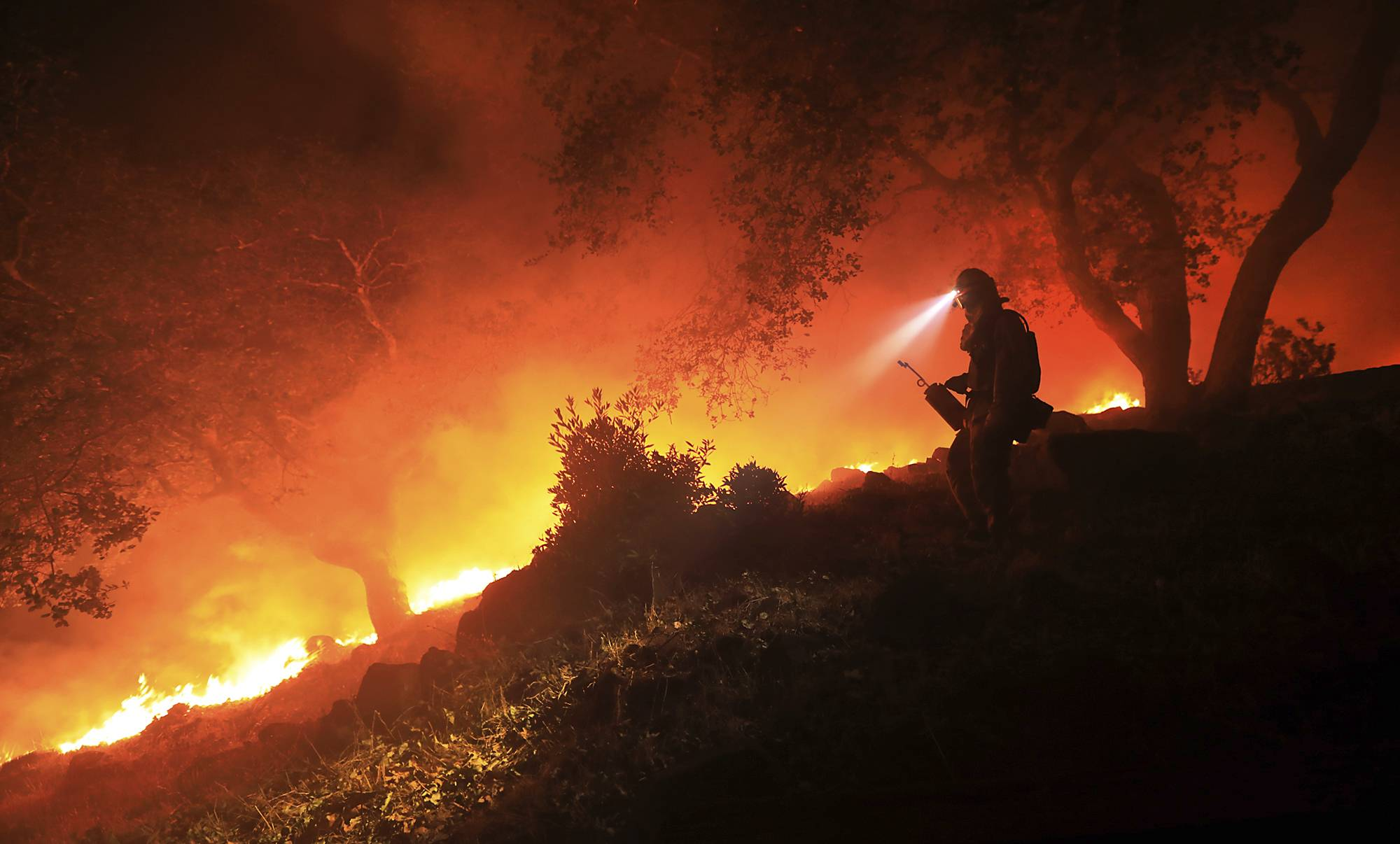 A San Diego Cal Fire firefighter monitors a flare up on a the head of a wildfire (the Southern LNU Complex), off of High Road above the Sonoma Valley, Wednesday Oct. 11, 2017, in Sonoma, Calif. A wind shift caused flames to move quickly up hill and threaten homes in the area. Three days after the fires began, firefighters were still unable to gain control of the blazes that had turned entire Northern California neighborhoods to ash and destroyed thousands of homes and businesses.