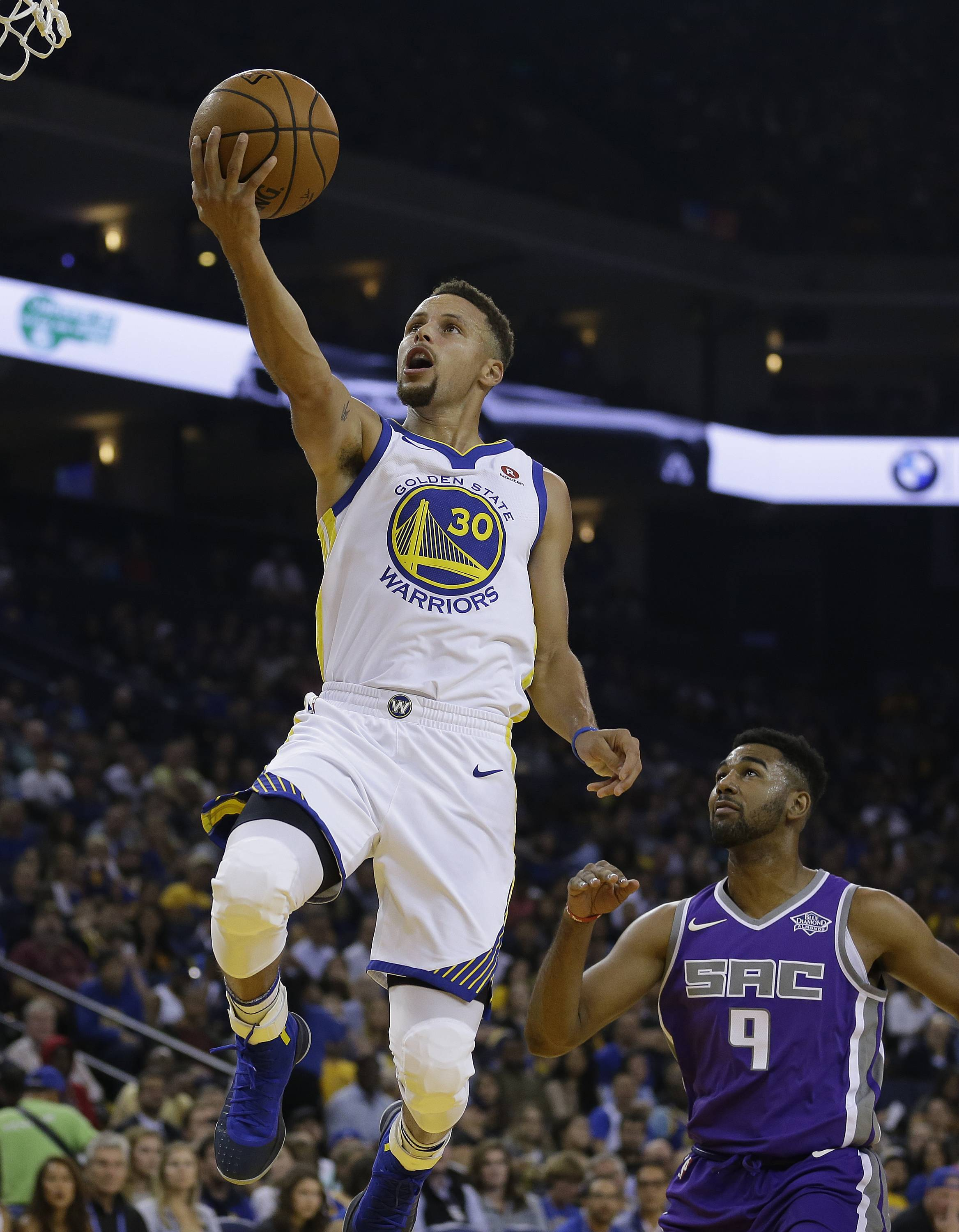 Golden State Warriors guard Stephen Curry, left, goes to the basket as Sacramento Kings guard Matt Jones, right, watches during the first half of a preseason NBA basketball game Friday, Oct. 13, 2017, in Oakland, Calif.