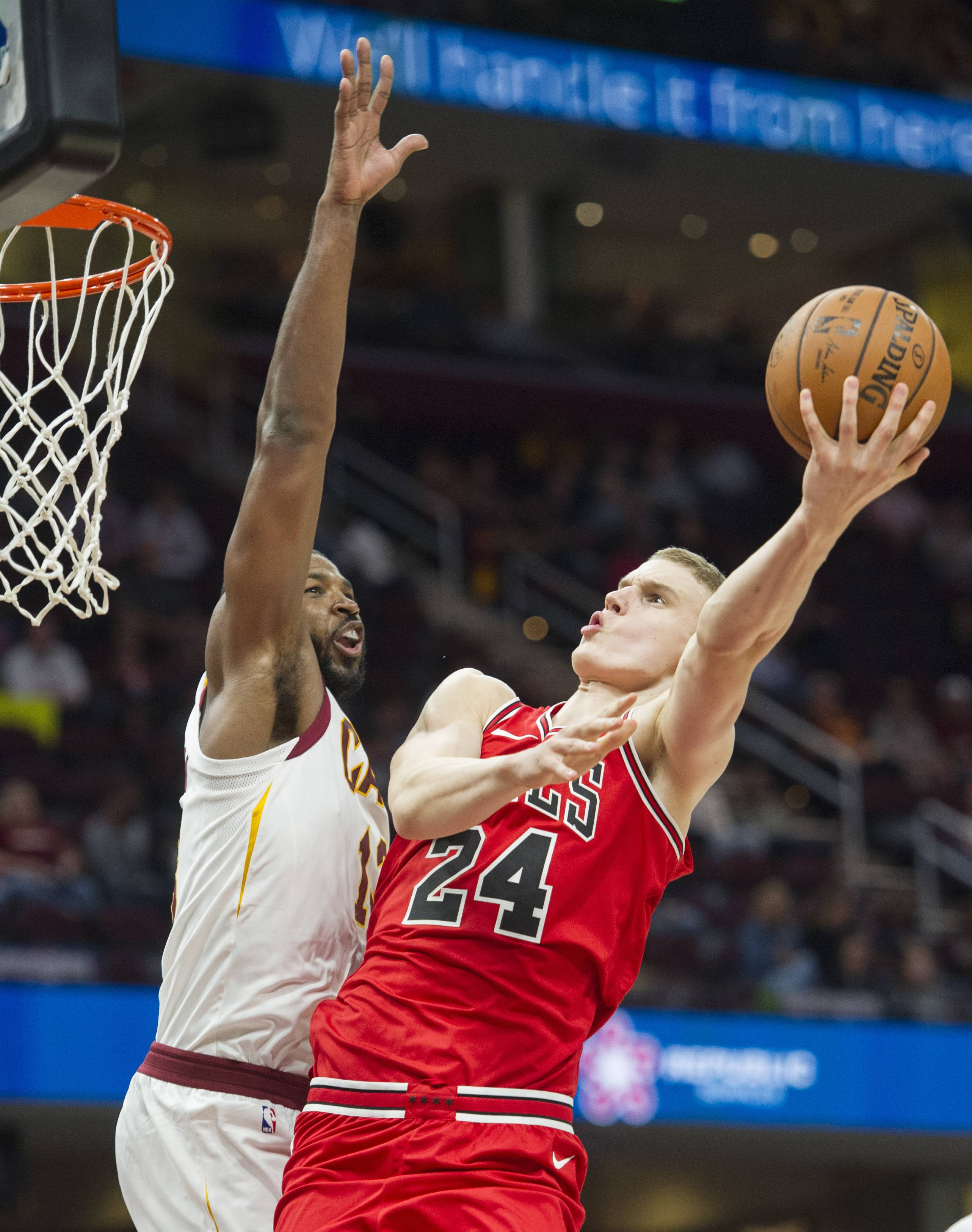 Chicago Bulls' Lauri Markkanen (24) shoots around Cleveland Cavaliers' Tristan Thompson during the second half of an NBA preseason basketball game in Cleveland, Tuesday, Oct. 10, 2017. The Bulls won 108-94. (AP Photo/Phil Long)