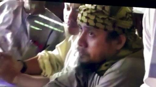 FILE - This file image taken from undated video shown to The Associated Press by the Philippine military shows the purported leader of the Islamic State group Southeast Asia branch, Isnilon Hapilon, right, at a meeting of militants at an undisclosed location. Philippine security officials told The Associated Press that Isnilon Hapilon, who is listed among the FBI's most-wanted terror suspects, and Omarkhayam Maute were killed in a gunbattle and their bodies were found Monday, Oct. 16, 2017 in Marawi. (Philippines Military via AP, File)
