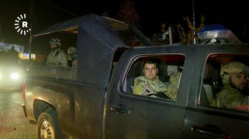 This image made from a video provided by RUDAW TV shows what the Irbil-based Kurdish broadcaster says are Peshmerga fighters and volunteers arriving on military trucks in Kirkuk, Iraq, Monday, Oct. 16, 2017. (RUDAW TV via AP)