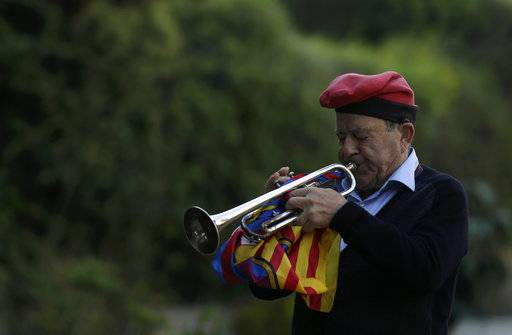 "A man wearing the traditional cup or ""barretina"" plays his trumpet during a ceremony commemorating the 77th anniversary of the death of Catalan leader Lluis Companys at the Montjuic Cemetery in Barcelona, Spain, Sunday, Oct. 15, 2017. Catalonia's separatist movement is being threatened by infighting over strategy to culminate its long-held desire to break away from Spain. Die-hard separatists are pushing for a definitive declaration of independence in the next few days. AP Photo/Manu Fernandez)"