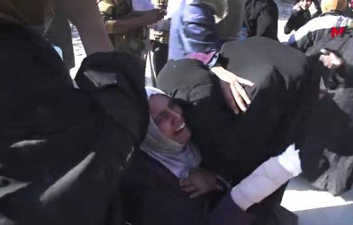 This frame grab from a video provided on Friday, Oct. 13, 2017 by Turkey-based Kurdish Mezopotamya agency media outlet that is consistent with independent AP reporting, shows an injured Syrian woman, center, reacts as she hugs another woman after they fled from the areas that still controlled by the Islamic State militants, in Raqqa, Syria. Scores of civilians including women and children are fleeing the last few remaining neighborhoods held by the Islamic State group in Syria's northern city of Raqqa, ahead of an anticipated final push by U.S.-backed fighters seeking to liberate the city. (Mezopotamya Agency, via AP)