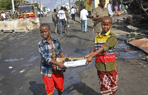 Somali children assist other civilians and security forces in their rescue efforts by carrying away unidentified charred human remains in a cardboard box, to clear the scene of Saturday's blast, in Mogadishu, Somalia, Sunday, Oct. 15, 2017. The death toll from the huge truck bomb blast in Somalia's capital rose to over 50 Sunday, with more than 60 others injured, as hospitals struggled to cope with the high number of casualties, security and medical sources said. (AP Photo/Farah Abdi Warsameh)