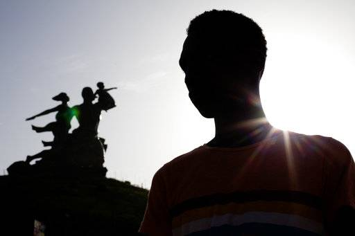 FILE- in this Oct. 2013 file photo, Alhaji,who fled Gambia after being beaten, tried, and persecuted for being gay, poses for a picture in front of the African Renaissance Monument in Dakar, Senegal. Defending gay rights can be dangerous in Africa, where many countries have laws against homosexuality. But activists in recent years stepped out of the shadows, empowered by the support of the Obama administration and the international community. Now many fear the Trump administration will undermine those gains, and that their exposure could make them more vulnerable. (AP Photo/Jane Hahn, file)