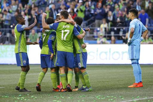 FC Dallas goalkeeper Jesse Gonzalez, right, looks on as Seattle Sounders players celebrate after forward Will Bruin (17) scored his second goal of the match during the second half of an MLS soccer match, Sunday, Oct. 15, 2017, in Seattle. The Sounders won 4-0. (AP Photo/Ted S. Warren)