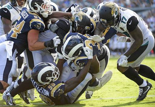 Los Angeles Rams' Malcolm Brown, center, runs over the goal line past Jacksonville Jaguars' Arrelious Benn (17) and others for a touchdown after he recovered a blocked punt during the first half of an NFL football game, Sunday, Oct. 15, 2017, in Jacksonville, Fla. (AP Photo/Phelan M. Ebenhack)