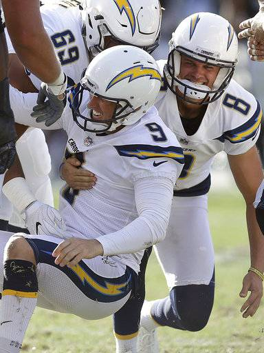 Los Angeles Chargers kicker Nick Novak (9) celebrates with Drew Kaser (8) and Sam Tevi (69) after making a winning field goal against the Oakland Raiders during the second half of an NFL football game in Oakland, Calif., Sunday, Oct. 15, 2017. (AP Photo/Ben Margot)