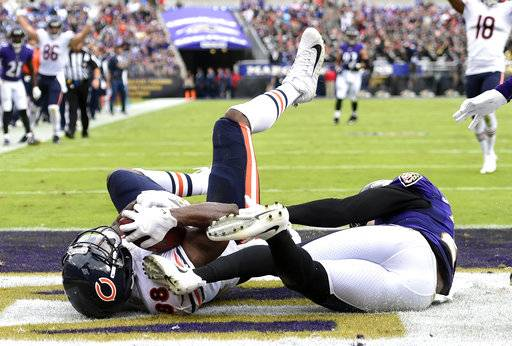 Chicago Bears tight end Dion Sims, left, scores a touchdown in front of Baltimore Ravens strong safety Tony Jefferson in the second half of an NFL football game, Sunday, Oct. 15, 2017, in Baltimore.