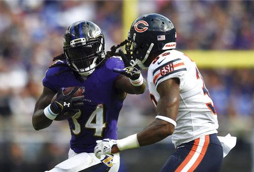 Baltimore Ravens running back Alex Collins, left, rushes against Chicago Bears free safety Eddie Jackson in the second half of an NFL football game, Sunday, Oct. 15, 2017, in Baltimore.