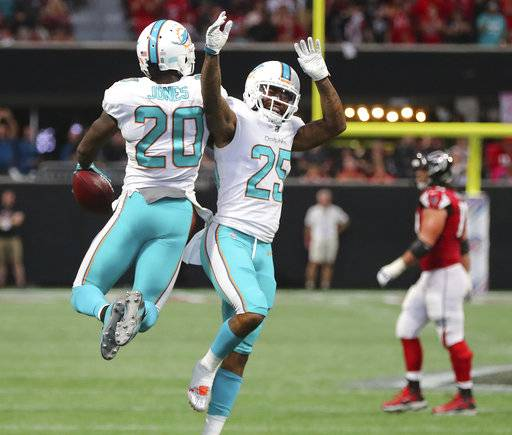Miami Dolphins safety Reshad Jones, left, celebrates with Xavien Howard after intercepting a pass from Atlanta Falcons' Matt Ryan during the final minute of an NFL football game Sunday, Oct. 15, 2017, in Atlanta.(Curtis Compton/Atlanta Journal-Constitution via AP)