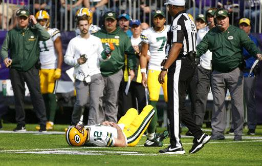 Green Bay Packers quarterback Aaron Rodgers (12) lies on the ground after being hit by Minnesota Vikings outside linebacker Anthony Barr (55) in the first half of an NFL football game in Minneapolis, Sunday, Oct. 15, 2017. (AP Photo/Bruce Kluckhohn)